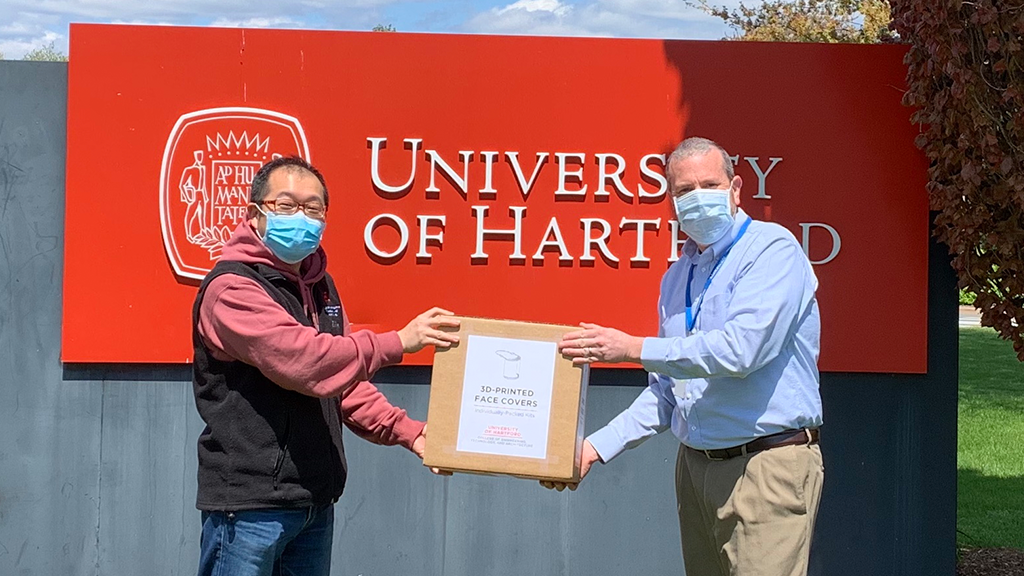 two man with box in front of uhart sign